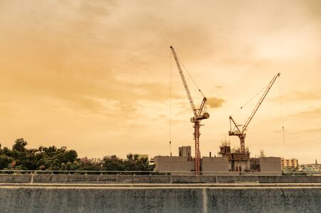 Crane and construction site working on building complex at sunset, developing city concept