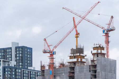 Crane and construction site working on building complex, developing city concept Standard-Bild