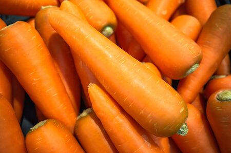 Pile of organic carrot in supermarket, vegetable background