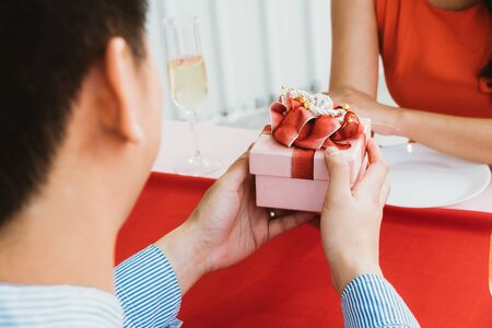 Asian man surprise his girlfriend with romantic present box, attractive couple sitting on dining table at restaurant, Valentine's dating day, birthday or anniversary concept