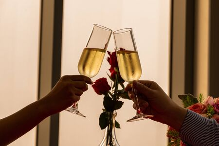 close up silhouette couple hand toasting champagne glass celebrating on Anniversary, New Year, birthday or Valentine. back to normal lifestyle. dinner dating together at home. banner with copy space