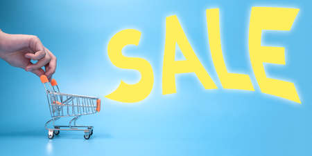 hand pushing shopping cart or trolley shouting SALE promotion for Big sale, discount or advertisement concept