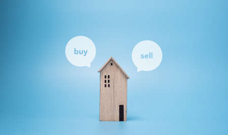wooden house toy with buy or sell for customer choice. real estate concept with copy space