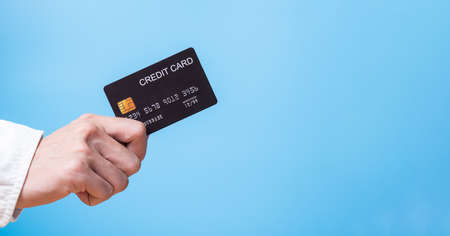 Banner advertisement of hand holding credit card for cashless payment or online shopping with copy space