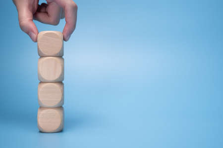 hand putting blank wooden block on stack for adding text, logo or symbol with copy space on background
