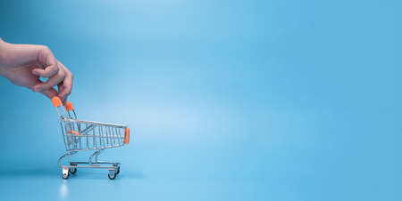 Banner of hand pushing shopping cart or shopping trolley on blue background. advertising use for adding text, message, copy space for sale promotion concept Standard-Bild