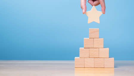 Banner of hand putting star on pyramid of stack wooden block. concept for reward, business, success process or career opportunity with copy space
