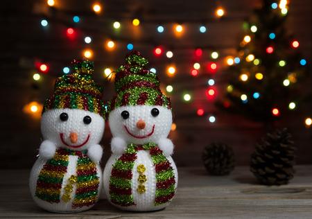 bonhomme de neige: couple de poup�es de bonhomme de neige sur la defocused de lumi�re de No�l et arbre de No�l arri�re-plan.