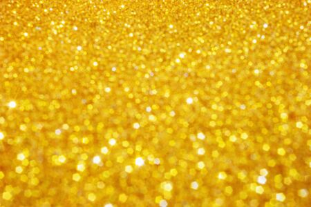 Defocused abstract colorful twinkle light background. Gold glittery bright shimmering background use as a design backdrop. Banque d'images