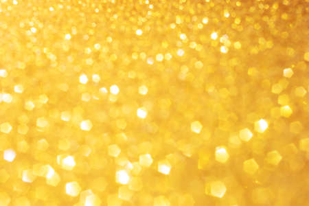Defocused abstract colorful twinkle light background. Gold glittery bright shimmering background use as a design backdrop.