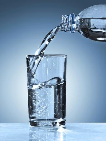 Glas en Fles met zuiver water op een blauwe achtergrond Stockfoto