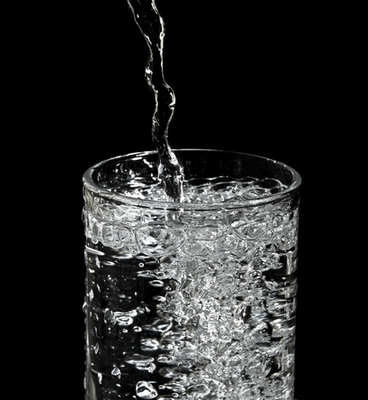 overflowing: filling water into glass and black background