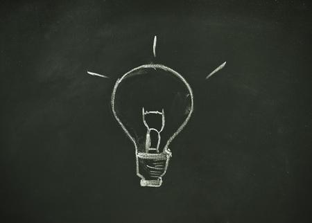drawing bulb by chalk on blackboard background  photo
