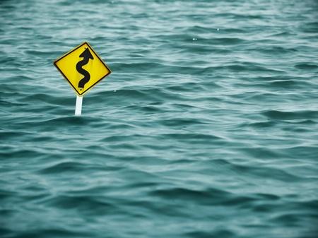 geel bord van de weg in het water
