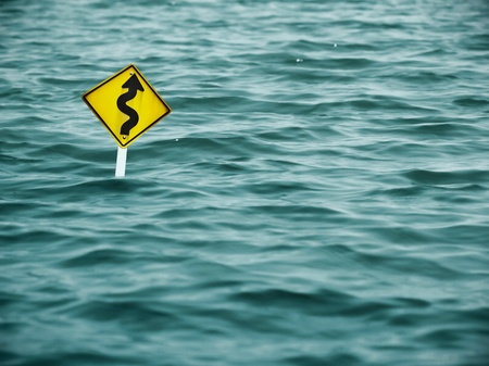 natural disaster: yellow sign of road in water Stock Photo