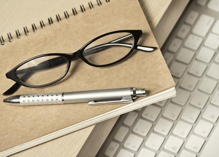 bril, pen en boek voor memo op bureau Stockfoto