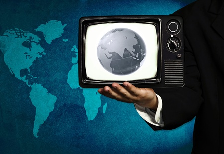 mass media: globe and tv in hand of business man (media intervention)