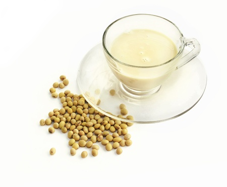 soy milk with raw soy beans over white photo