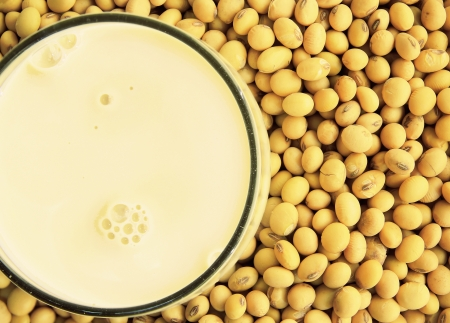 soy milk with raw soy beans background