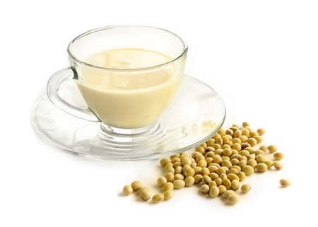 soy milk with raw soy beans over white