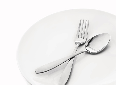 plate with spoon and fork on white