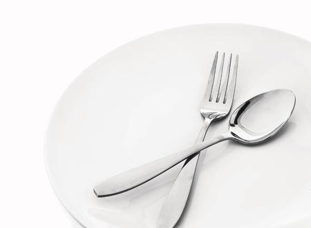 plaat met lepel en vork op wit Stockfoto
