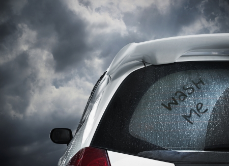 car side: a dirty car waiting under dark cloud and to be washed Stock Photo