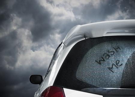 lavado: un coche sucio esperando bajo la nube oscura y lavarse Foto de archivo