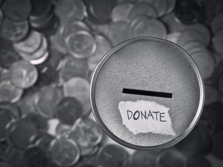 dar un regalo: donación de caja con las monedas en tono monocorde Foto de archivo