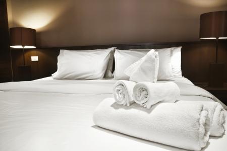 chambre à coucher: serviettes blanches préparées sur le lit Banque d'images