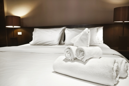 white towels prepared on bed photo