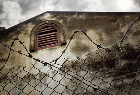 prison fence: barbed wire fence and prison building
