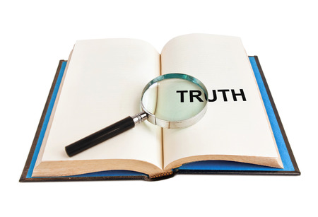 magnifying glass and word truth on book photo
