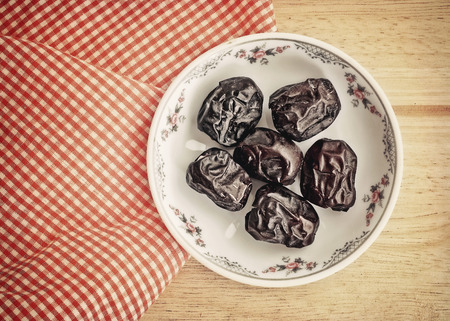 Ajwa Dates fruit in retro style (Ajwa is a soft dry variety of date fruit from Saudi Arabia. It is cultivated at the city of Madinah)