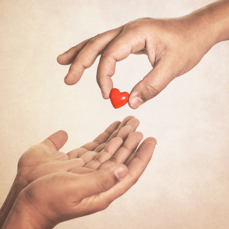 donate: Share your love (hand giving a heart in vintage style)