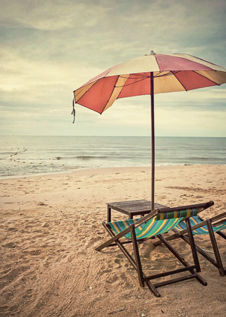 chairs and umbrella on the beach  retro style  photo