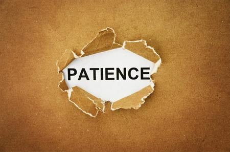 """paciencia: la palabra """"paciencia"""" en el agujero de papel marr�n Foto de archivo"""