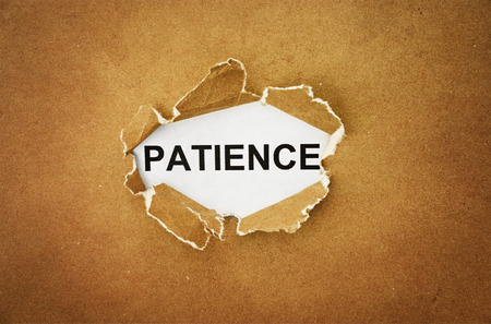 rend: the word patience in the hole of brown paper Stock Photo