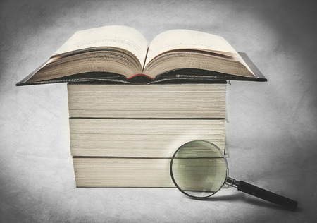 magnifying glass and books in retro style photo