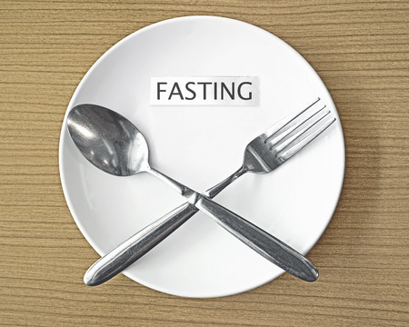 diet concept: fasting paper and fork with spoon symbol on white plate