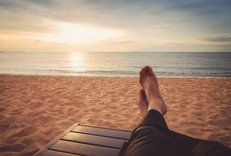 man ontspannen op de zonsondergang strand (retro-stijl)
