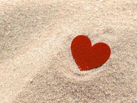 red heart shape on sand photo