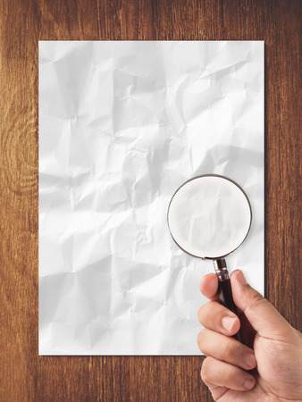 looking in white crumpled paper and wooden background photo