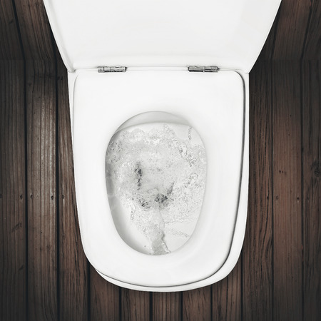a flush toilet on wood floor Stock Photo