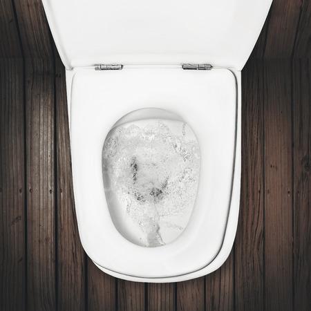a flush toilet on wood floor Stockfoto