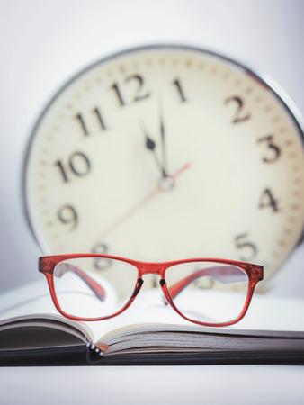 Rode bril op het boek (opblijven studeren) Stockfoto - 42309917