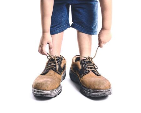chaussure: enfant dans de gros souliers sur fond blanc Banque d'images