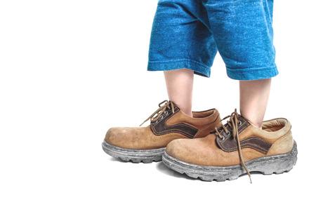 kid in big shoes on white background Foto de archivo