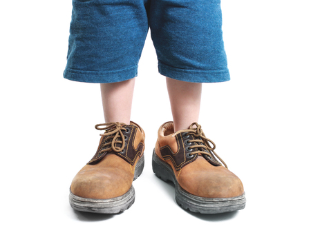 wearing: kid in big shoes on white background Stock Photo