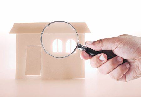 house inspection: a hand holding magnifying glass looking for a house Stock Photo